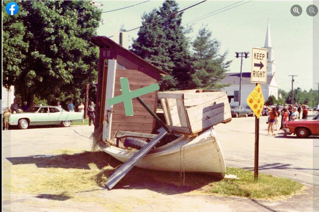 photo of a large item trash pile on the side of a road. A street sign and small boat are part of the pile, as is what appears to be an outhouse.