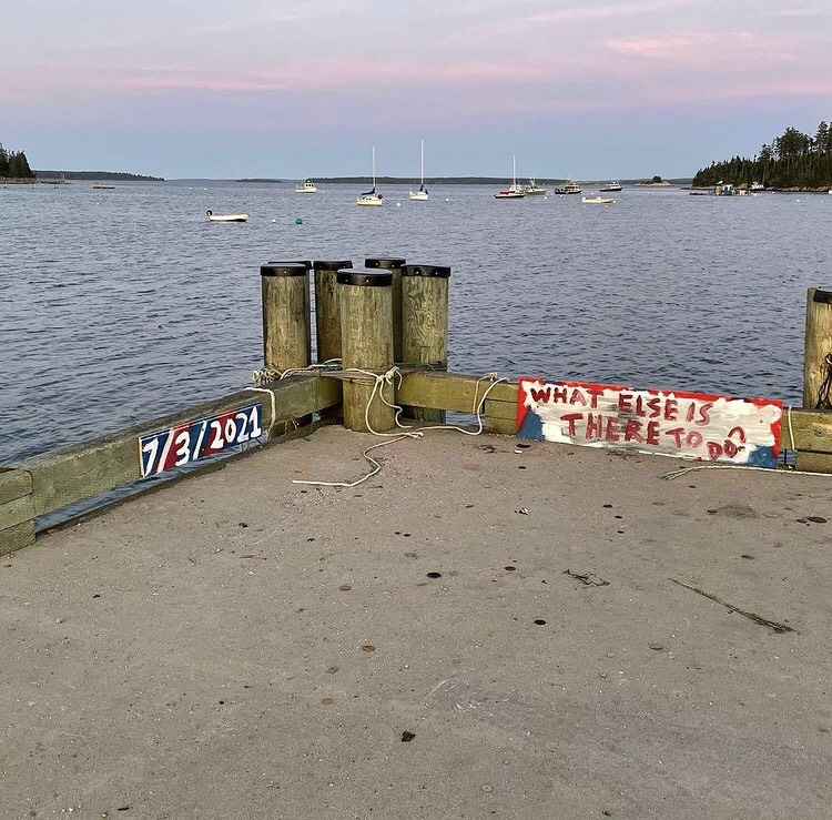The end of a dock with a beautiful pink and blue sunset behind it. Painted on the dock is