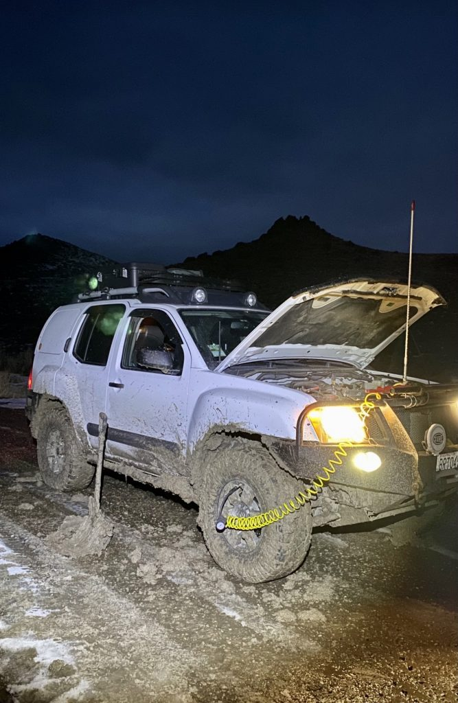 A Nissan Xterra parked at night in dirt with the hood open. The headlights are on and there is a cord extending from a front wheel to inside the hood.