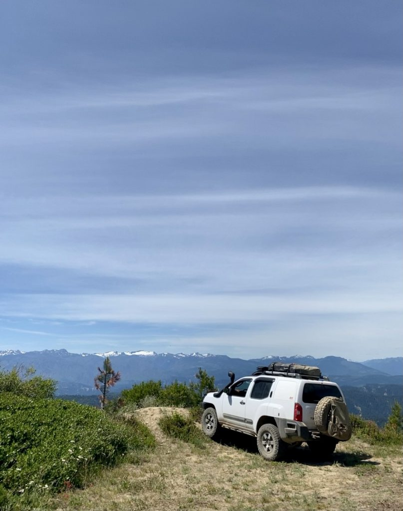 A Nissan Xterra parked at a cliff overlooking a mountain view