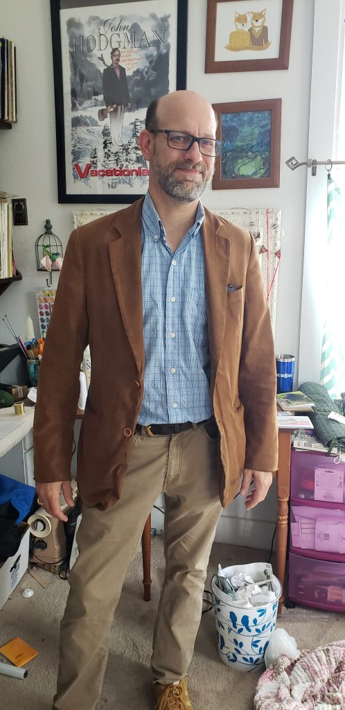 A man posing in a home office with a light brown corduroy blazer