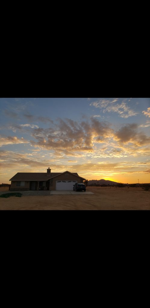 A house in a desert, with nothing around it and a colorful sunset behind it.