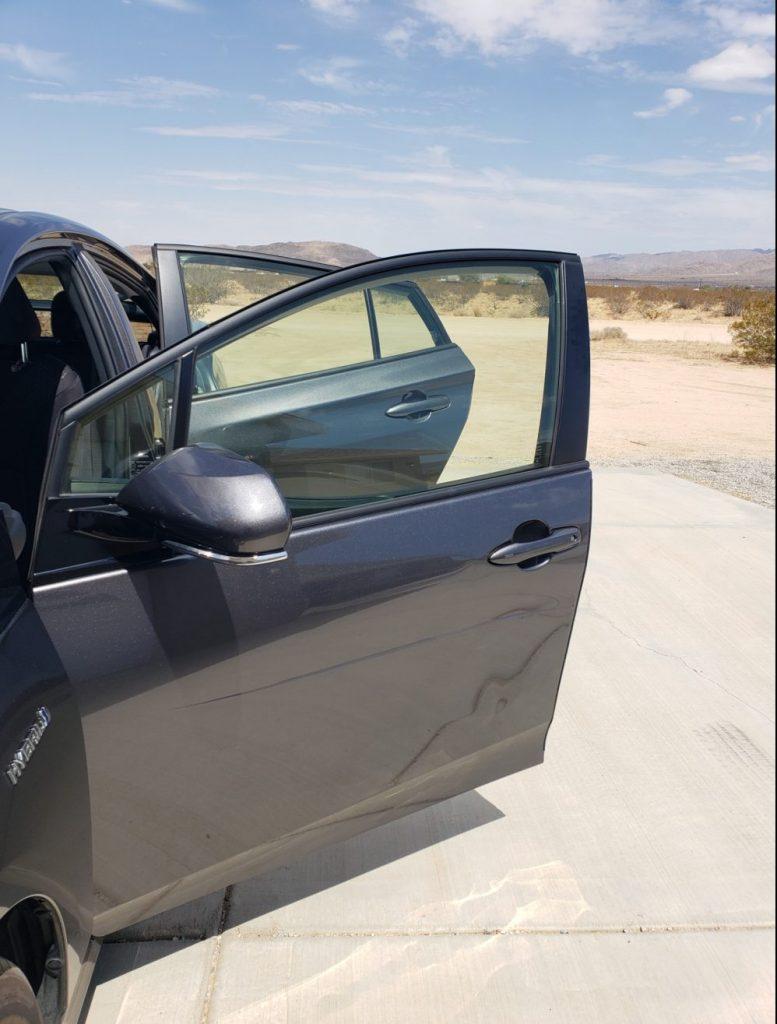 An open gray Prius door with a dent in it